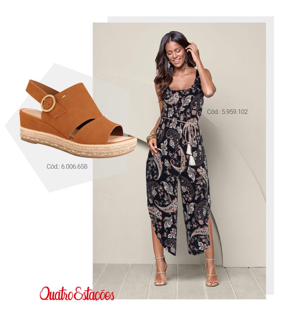 Modelo vestindo um macacão pantacourt marinho com estampas de mandalas  e amarração na cintura. Sugestão de combinação com sandália cor caramelo.