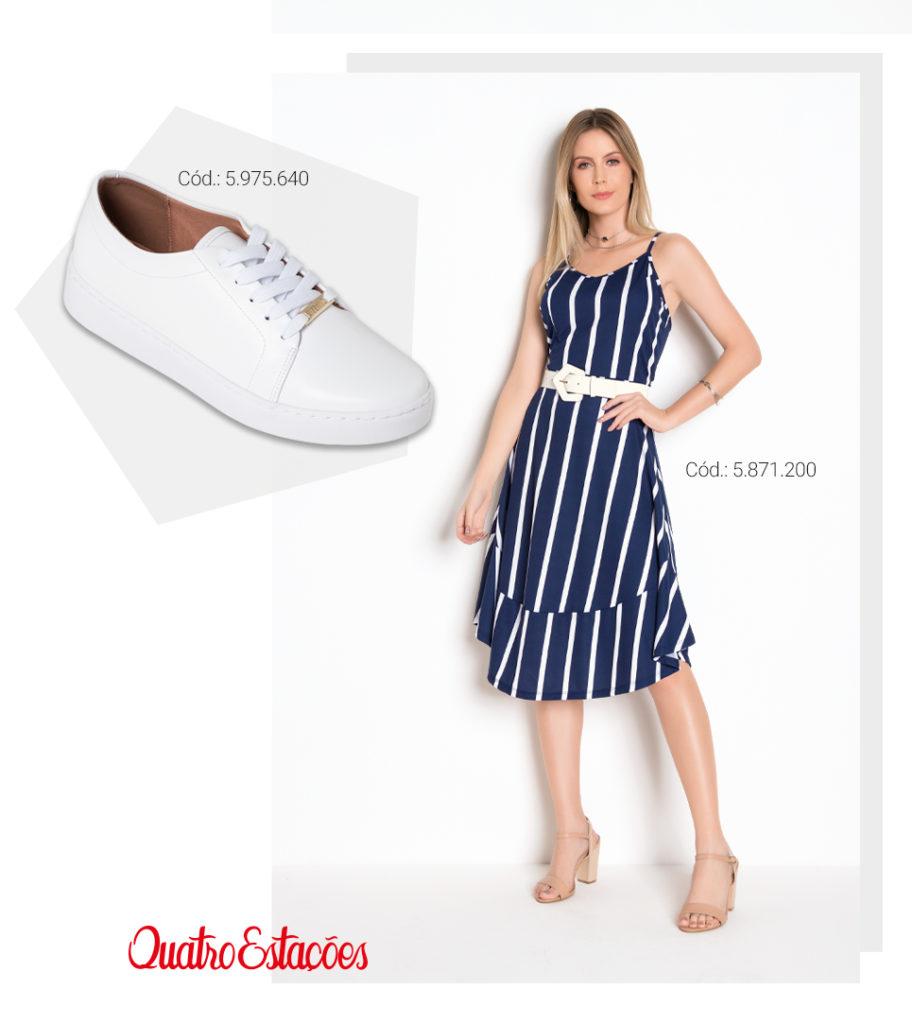 Modelo usando um vestido mídi de alças, cor marinho com listras verticais na cor branca. Sugestão de combinação com tênis branco.